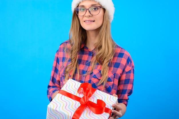 Linda garota de camisa xadrez e óculos segurando uma caixa de presente