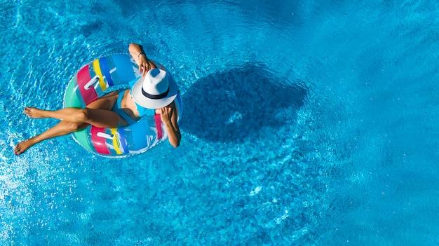Linda garota de chapéu na piscina aérea vista superior de cima, jovem relaxa e nada no anel inflável donut e se diverte na água em férias em família, estância de férias tropical