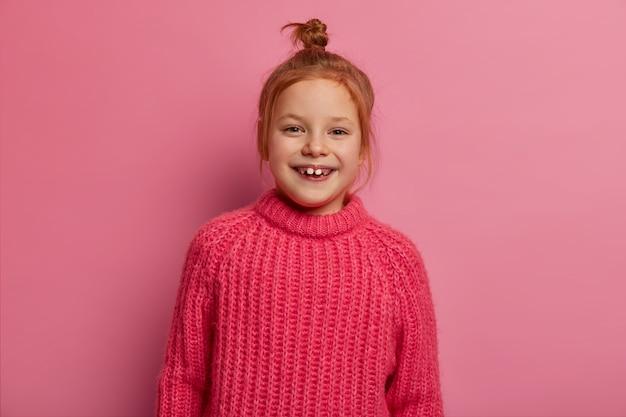 Linda garota de cinco anos posa, expressa emoções positivas, tem cabelo ruivo, usa um suéter quente de inverno, feliz por ser fotografada, posa contra a parede rosa. emoções sinceras e crianças.