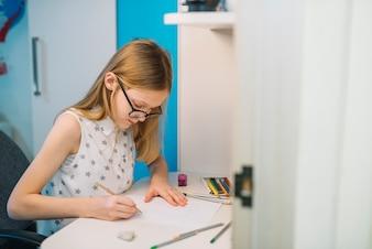 Linda garota de desenho com lápis na mesa branca