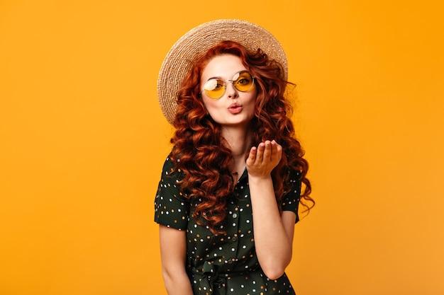 Linda garota de gengibre enviando beijo no ar sobre fundo amarelo. foto de estúdio de jovem encaracolado em óculos escuros e chapéu de palha.