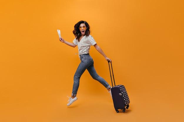 Linda garota de jeans está pulando em fundo laranja. retrato de corpo inteiro de mulher com ingressos e mala