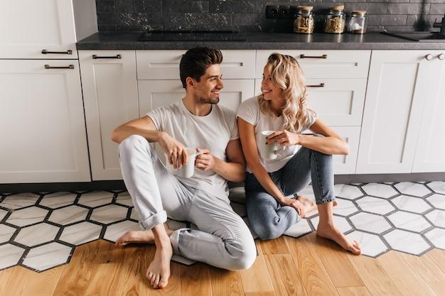 Linda garota de jeans, sentada no chão e conversando com o namorado. jovem casal desfrutando de café na cozinha.