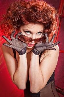 Linda garota de lingerie preta fica em uma escada sobre um fundo vermelho.