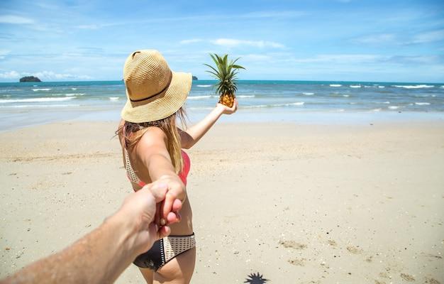 Linda garota de maiô e abacaxi caminha na praia segurando a mão do cara