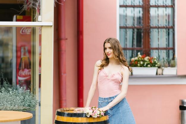 Linda garota de modelo bonito de pernas longas em pé perto de um barril de carvalho decorativo na cidade num dia de verão