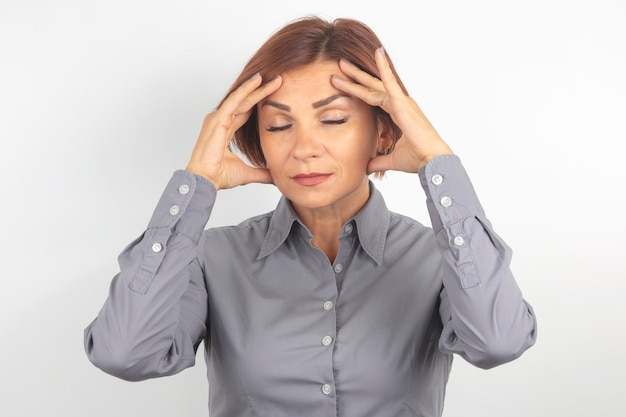 Linda garota de negócios com os olhos fechados pensa sobre seu projeto em uma superfície branca