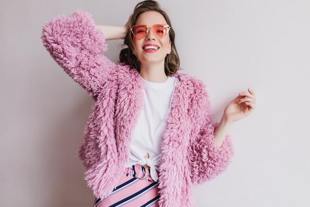 Linda garota de óculos de sol rosa posando com um sorriso alegre na parede branca. retrato interior de mulher de cabelo curto com casaco de pele, brincando com seu cabelo.
