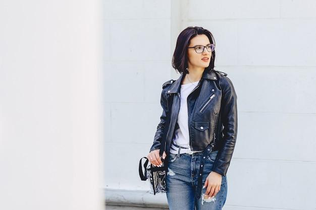 Linda garota de óculos em roupas elegantes, luz de fundo lá fora