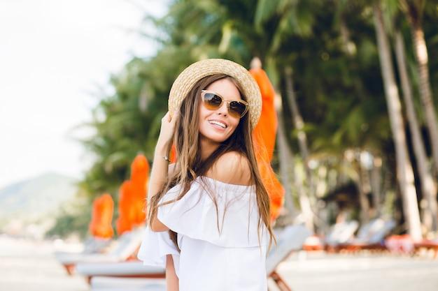 Linda garota de óculos escuros marrons e chapéu de palha sorri com charme.