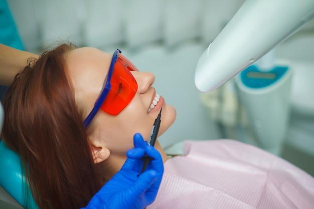 Linda garota de óculos protetores vermelhos sentado em uma cadeira azul no escritório do dentista.