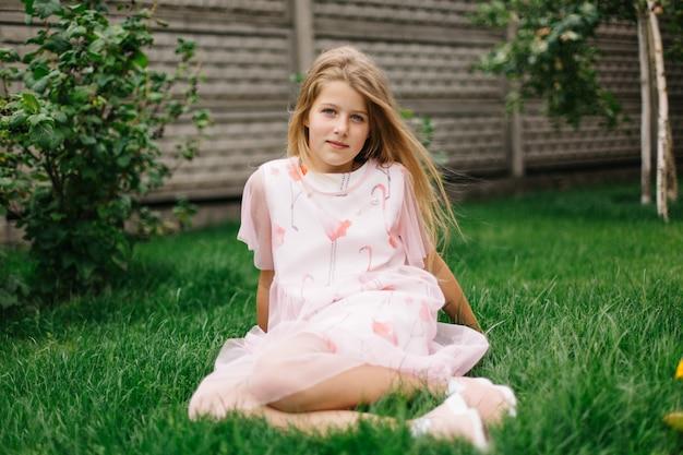 Linda garota de olhos azuis, com longos cabelos loiros. menina em um vestido rosa flamingo. verão brilhante, foto emocional. modelo de menina com cabelo comprido senta-se na grama verde