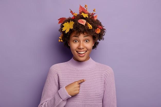 Linda garota de outono aponta para si mesma, feliz por ter sido escolhida para participar do festival sazonal, usa suéter tricotado quente, folhas coloridas, frutas e flores no cabelo, isolado no fundo roxo
