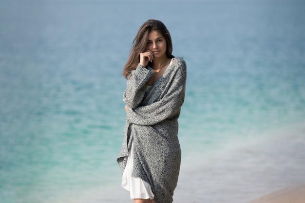 Linda garota de pé à beira do lago. retrato do estilo de vida na natureza.