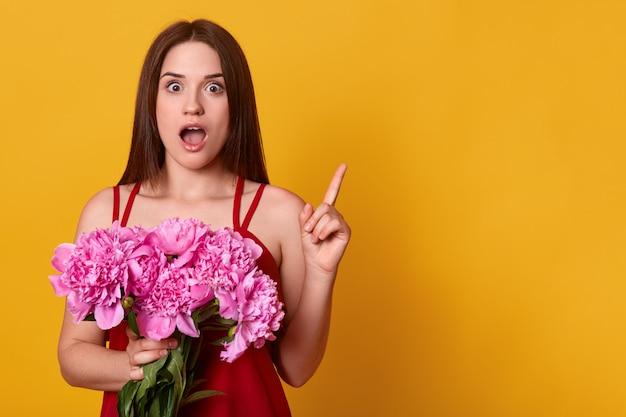 Linda garota de pé com buquê de peônias rosadas nas mãos dela