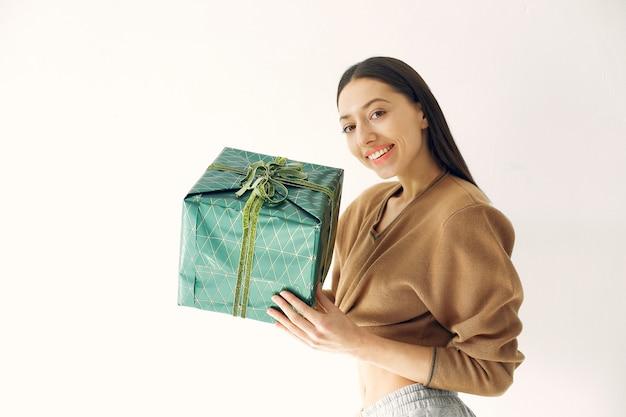 Linda garota de pé em um estúdio com presentes