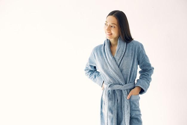 Linda garota de pé em um estúdio em um roupão azul