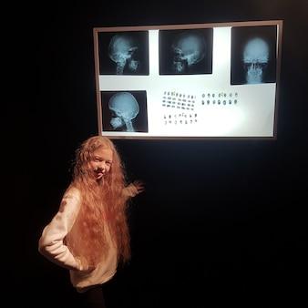 Linda garota de pé em um quarto escuro perto do negatoscópio.