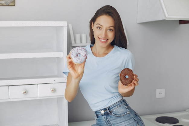 Linda garota de pé em uma cozinha com rosquinha