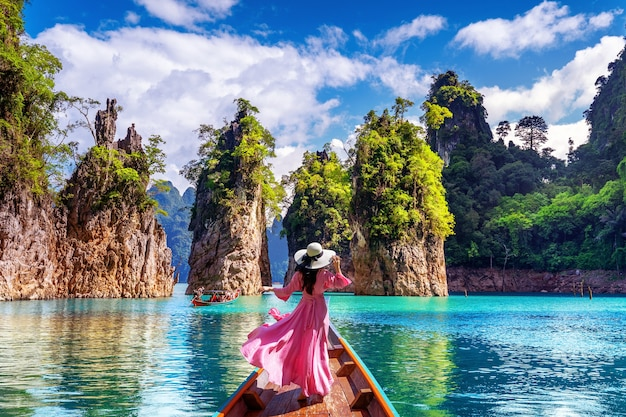 Linda garota de pé no barco e olhando para as montanhas na barragem de ratchaprapha no parque nacional khao sok, província de surat thani, tailândia.