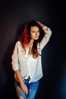 Linda garota de pé perto da parede azul escura na escuridão