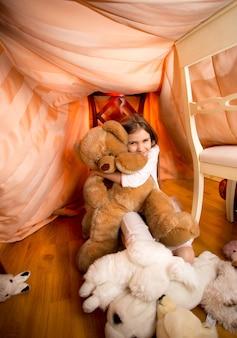 Linda garota de pijama brincando com um ursinho de pelúcia no quarto