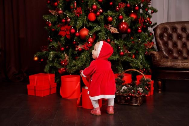 Linda garota de um ano de idade com fantasia de papai noel no fundo da árvore de natal decorada com brinquedos. criança em decorações com caixas de presente. conceito de celebração do ano novo em casa aconchegante. copie o espaço