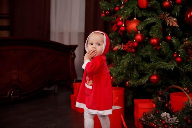 Linda garota de um ano de idade fantasiada de papai noel sobre a árvore de natal decorada com brinquedos. criança em decorações com caixas de presente