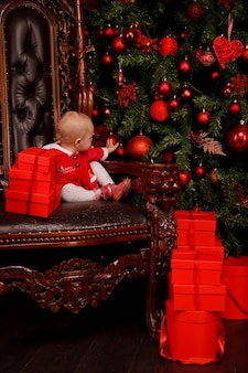 Linda garota de um ano de idade no vestido de papai noel no trono no fundo da árvore de natal decorada brinquedos. criança em decorações com caixas de presente. conceito de celebração do ano novo em casa aconchegante. copie o espaço