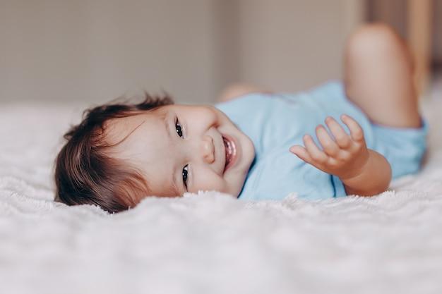 Linda garota de um ano de idade rindo, deitado na cama e olhando para a câmera tocar seus pés