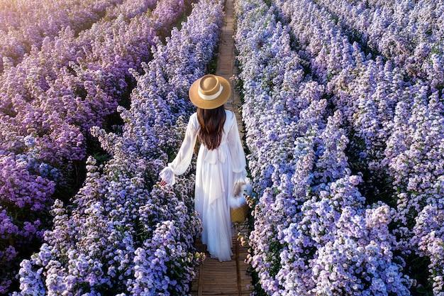 Linda garota de vestido branco andando nos campos de flores de margaret