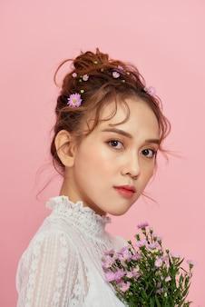 Linda garota de vestido branco com flores nas mãos em uma rosa
