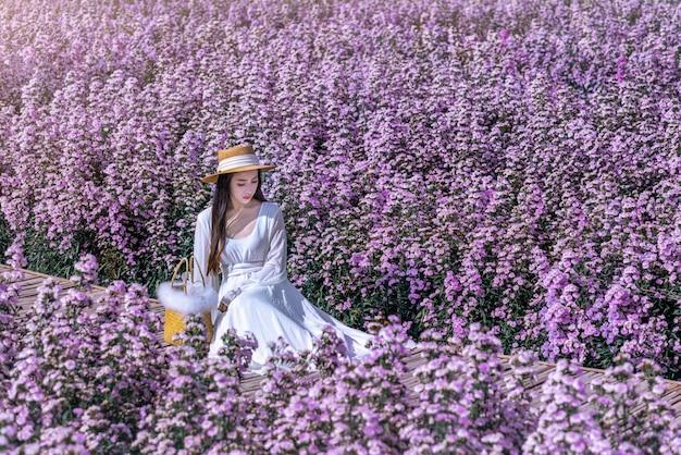 Linda garota de vestido branco sentada em um campo de flores de margaret