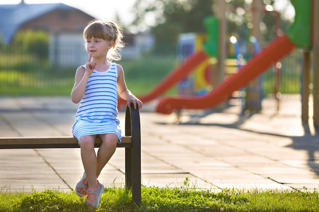 Linda garota de vestido curto, sentado sozinho ao ar livre no banco do recreio