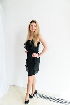 Linda garota de vestido preto em um fundo branco.