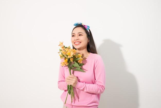 Linda garota de vestido rosa com flores nas mãos