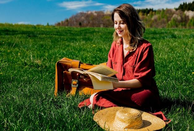 Linda garota de vestido vermelho e chapéu com mala e livro sentado no prado. temporada de primavera