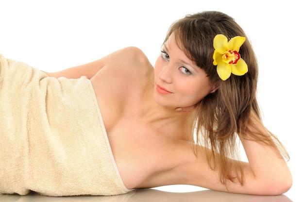 Linda garota deitada em uma toalha em uma parede branca, uma flor amarela é espetada em seu cabelo, saúde e tema de spa