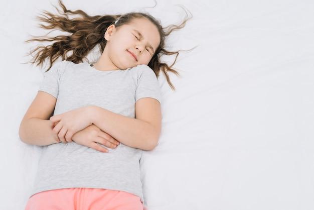Linda garota deitada na cama branca, sofrendo de dor de estômago