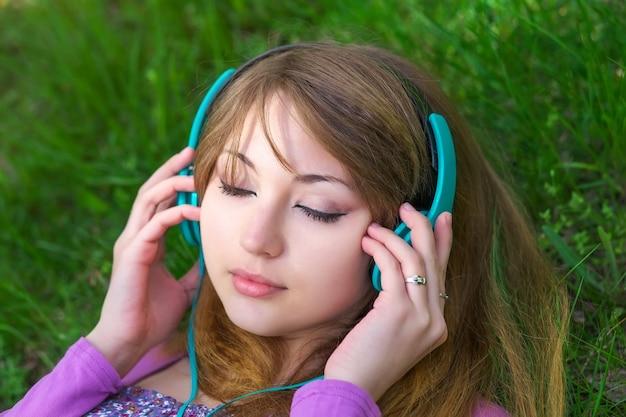 Linda garota deitada na grama ouvindo música com fones de ouvido no parque