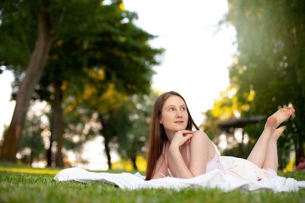 Linda garota deitada na grama verde com uma esteira no parque e olhando para cima pensativa