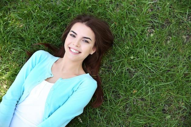 Linda garota deitada na grama verde