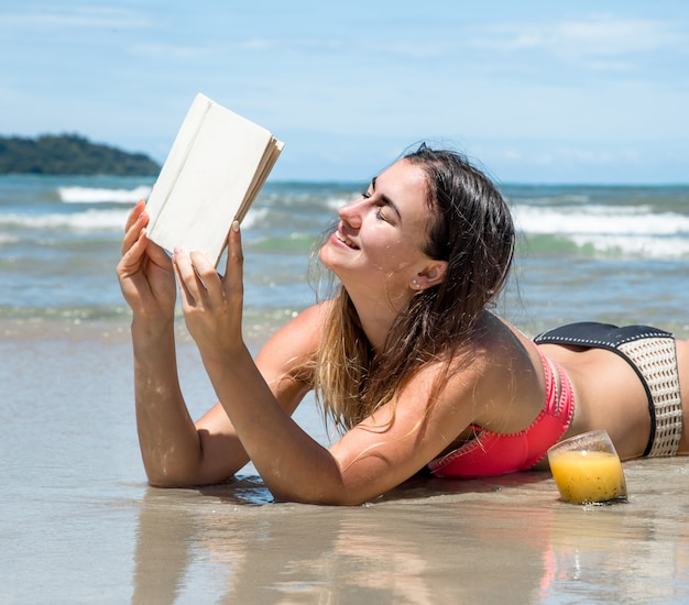 Linda garota deitada na praia lendo um livro com bebidas frescas no verão e frutas tropicais, férias