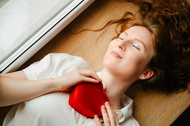 Linda garota deitada perto da janela com um presente para o dia dos namorados. cabelo ruivo cacheado e solto. close up de tiro superior.