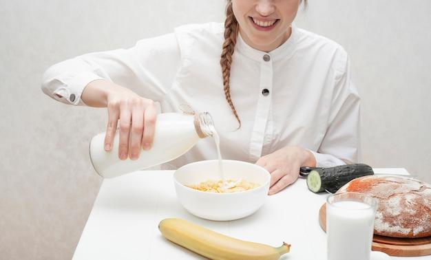 Linda garota derramando leite em uma tigela com cereais