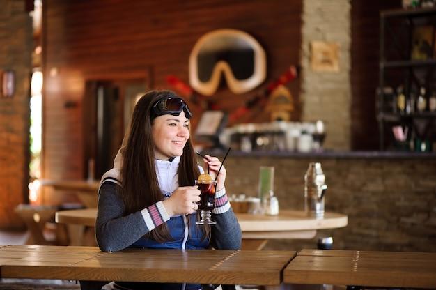 Linda garota descansando e bebendo vinho quente gostoso com quentão em um café da estação de esqui