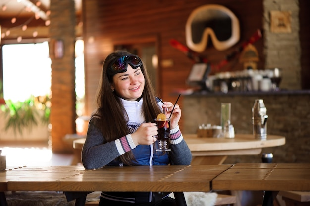 Linda garota descansando e bebendo vinho quente quente com especiarias em um café resort de esqui