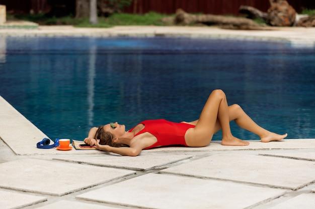 Linda garota descansando perto da piscina