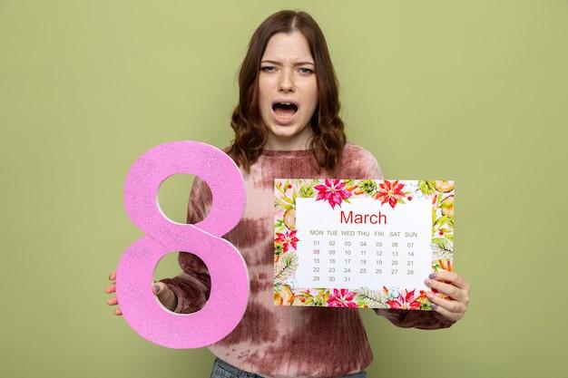 Linda garota descontente no feliz dia da mulher segurando o número oito com o calendário