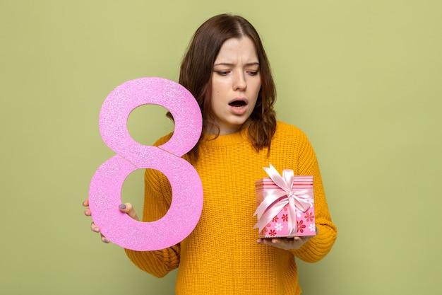 Linda garota descontente no feliz dia da mulher segurando o número oito, olhando para o presente na mão